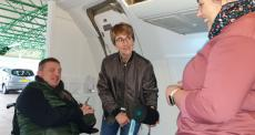 Disabled man and his wife in a mock aircraft cabin talking to a smiling lady