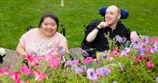man and lady in wheelchairs enjoying garden
