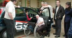 people standing around car and driver with wheelchair