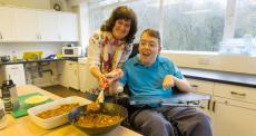 person with disability cooking with a helper