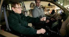 lady learning to drive a modified vehicle alongside instructor