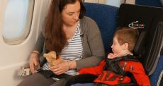 boy in support seating on a plane next to adult