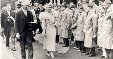Historical photo of the Queen Mother walking past parade of disabled people