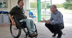 man in wheelchair talking with staff member