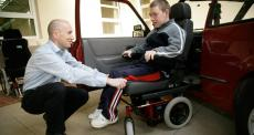 man in wheelchair receiving guidance to improve access to a car and on seating and posture