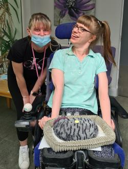 Chelsea with a face mask next to a smiling lady in a wheelchair